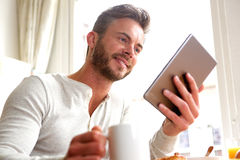 Smiling man by window with tablet and coffee Royalty Free Stock Photography