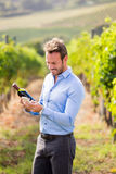 Smiling man with wine bottle using phone Stock Images
