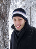 Smiling man in winter park. Portrait of young handsome man smiling in winter park royalty free stock photography