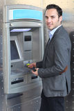 Smiling man withdrawing money at ATM Stock Photos