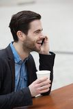 Smiling man withmobile phone outdoors Stock Photos