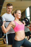 Smiling man and woman with barbell in gym Stock Photography