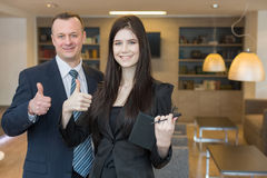 Smiling man and woman in business suits doing a thumbs up Royalty Free Stock Image