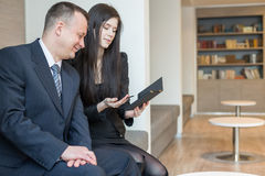 Smiling man and woman in business suits sitting with notepad Stock Photos