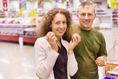 Smiling man and woman buy peaches in supermarket Stock Photos