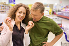 Smiling man and woman buy peaches in supermarket. Smiling young man and woman buy peaches in supermarket Stock Photos