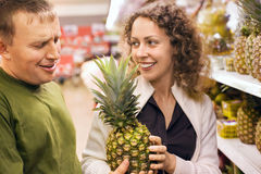 Smiling man and woman buy pineapple in supermarket. Smiling young man and woman buy pineapple in supermarket stock photos
