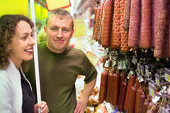 Smiling man and woman buy sausage in supermarket Royalty Free Stock Images