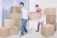 Smiling man and woman carry box together Stock Image