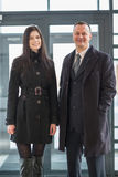 Smiling man and woman in a coat stand Stock Image