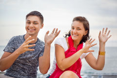 Smiling man and woman dancing sitting on beach Royalty Free Stock Photography
