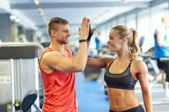Smiling man and woman doing high five in gym Stock Photos