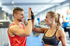 Smiling man and woman doing high five in gym Stock Images
