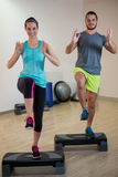 Smiling man and woman doing step aerobic exercise on stepper Stock Photos