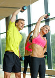Smiling man and woman with dumbbells in gym Royalty Free Stock Photos