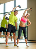 Smiling man and woman with dumbbells in gym Stock Photography
