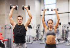 Smiling man and woman with dumbbells in gym Stock Photos