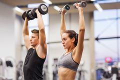 Smiling man and woman with dumbbells in gym Stock Images