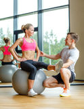 Smiling man and woman with exercise ball in gym Royalty Free Stock Photo