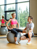 Smiling man and woman with exercise ball in gym Royalty Free Stock Image