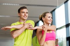 Smiling man and woman exercising in gym stock image