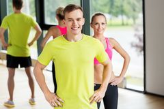 Smiling man and woman exercising in gym royalty free stock photo