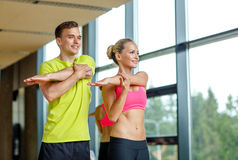 Smiling man and woman exercising in gym Stock Photos