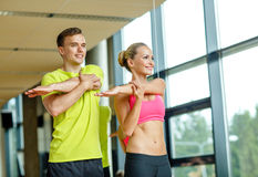 Smiling man and woman exercising in gym Stock Photo