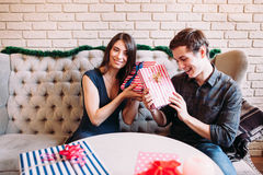 Smiling man and woman guessing gifts, free space Stock Photography
