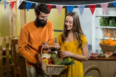 Man and woman holding a basket of vegetables at the grocery store. Smiling man and woman holding a basket of vegetables at the grocery store royalty free stock photos