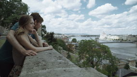 Smiling man and woman looking at the city from above stock video footage