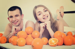 Smiling man and woman lying with orange fruits Royalty Free Stock Images