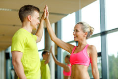 Smiling man and woman making high five in gym Stock Images