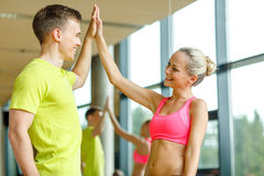 Smiling man and woman making high five in gym Stock Photography