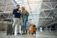 Smiling man and woman paying for boarding pass. Low angle of happy couple using modern technology to purchase electronic ticket for plane. Their suitcases Royalty Free Stock Image