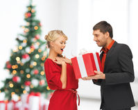 Smiling man and woman with present. Winter, holidays, christmas, celebration and people concept - smiling men and women with present over living room with Royalty Free Stock Photos