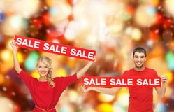 Smiling man and woman with red sale signs Stock Images