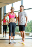 Smiling man and woman with scales in gym Royalty Free Stock Photos