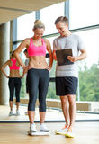 Smiling man and woman with scales in gym Stock Images