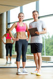 Smiling man and woman with scales in gym Royalty Free Stock Photo