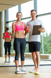 Smiling man and woman with scales in gym Stock Photos
