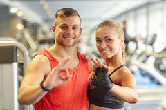 Smiling man and woman showing ok hand sign in gym Stock Photography