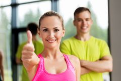 Smiling man and woman showing thumbs up in gym royalty free stock image
