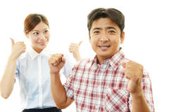 Smiling man and woman showing thumbs up sign Royalty Free Stock Image