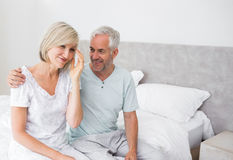 Smiling man and woman sitting on bed Royalty Free Stock Image