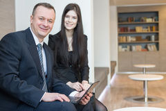 Smiling man and woman sitting with a laptop royalty free stock photo