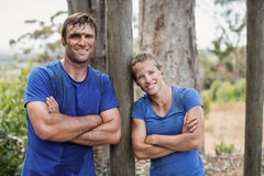 Smiling man and woman standing with arms crossed during obstacle course. Smiling men and women standing with arms crossed during obstacle course in boot camp royalty free stock photography