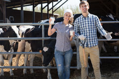 Smiling man and woman standing with in the cow hangar and showin Royalty Free Stock Photos