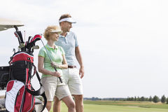 Smiling man and woman standing at golf course against clear sky. Smiling men and women standing at golf course against clear sky Royalty Free Stock Photo