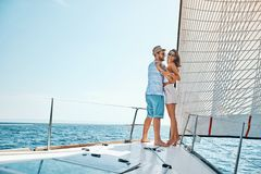 Smiling man and woman traveling on vacation sailing on open sea ocean enjoying romance royalty free stock photos